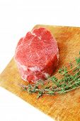 fresh red meat : raw beef fillet on wooden board with thyme ready to prepare . isolated over white b