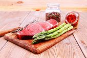 prime fillet meat : dry raw beef on cutting board with asparagus , thyme bundle , color peppercorn m
