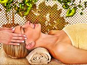 Woman getting head massage in tropical beauty spa.