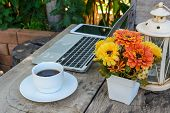 picture of keypad  - a cup of coffee and laptop on wood floor with flower