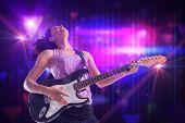 Pretty girl playing guitar against digitally generated cool nightlife design