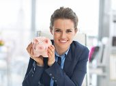 Portrait Of Happy Business Woman Showing Piggy Bank