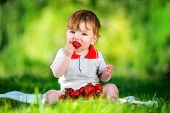 Happy Baby Have Fun In The Park On A Sunny Meadow With Strawberry. Summer Vacation Concept. The Emot