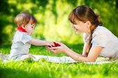 Happy Family, Mom And Little Son Having Fun In The Park. Raspberry In His Hands. Summer Vacations Co