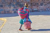 CUZCO, PERU, MAY 1, 2014 - Woman in traditional costume, with hat and manta shawl,, walks carrying a bag