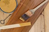 stock photo of shingles  - Closeup top view of painting tools consisting of hand brush stir stick can opener and paint lid on cedar wooden shingles with top board stained and unstained boards underneath - JPG