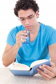 Man Reading Book While Drinking Healthy Water From A Glass
