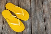 Colorful flip-flops on wooden background