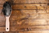 Wooden hairbrush on wooden background