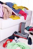Messy colorful clothing on  sofa on light background