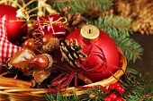 Christmas decorations in basket and spruce branches on table close up