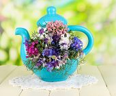 Beautiful bouquet in blue teapot on wooden table on natural background