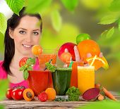Young happy woman with Fresh juice mix fruit, healthy drinks on wooden table.