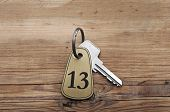 Closeup of an key of room number 13 with key on a wooden desk