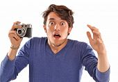 Surprised photographer holding a photographic camera.Expressive photographer.