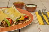 Burritos Filled With Ground Beef And Peppers, Topped With Cheese