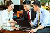 Three Asian Chinese office people or businessmen and businesswoman having a business meeting in a ho