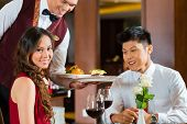 Asian Chinese couple - Man and woman - or lovers having a date or romantic dinner in a fancy restaur