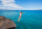 Man jumping off cliff into the ocean. Summer fun lifestyle.