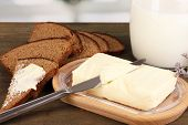 Butter on wooden holder surrounded by bread and milk on wooden table on window background