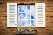 Open Old Window With Flower Basket On Brick Wall
