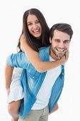 Happy hipster giving his girlfriend a piggy back on white background