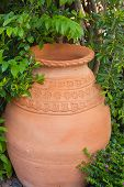 picture of slut  - Pottery jars in a garden with trees - JPG