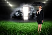Young businesswoman holding umbrella against football pitch with bright lights