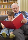 stock photo of storytime  - grandfather reading a story to his grandchild - JPG