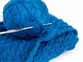 Blue yarn ball, crochet piece and crochet hook