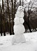 picture of sad christmas  - Sad Christmas snowman sitting in a snowy outdoors - JPG