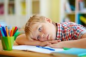 Bored or pensive schoolboy lying on desk