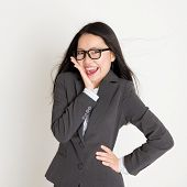 Surprised Asian business woman looking at camera and smiling, standing on plain background.