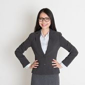 Young Asian business woman smiling at camera, standing on plain background.