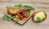 Roasted Leg Of Lamb With Vegetables And Herbs On A Wooden Background