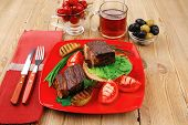 roast meat : beef (pork) steak garnished with vegetables , juice and olives on red plate over wooden table