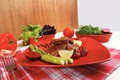 grilled beef pork meat served on red plate with asparagus hot pepper salad and bell on napkin over white wooden table