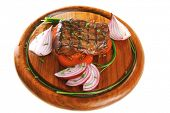 roasted fillet served with tomato on wooden plate