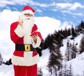 christmas, holidays and people concept - man in costume of santa claus with notepad and pen over snowy mountains background
