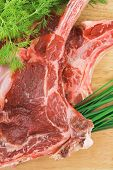 raw meat : boned fresh ribs served with dill and green chives on wooden board isolated over white background