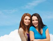 happiness, friendship and people concept - smiling teenage girls hugging over blue sky and cloud background