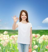 advertising, childhood, nature, gesture and people concept - smiling girl in white t-shirt showing ok sign over flower field background