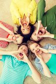education and happiness concept - group of young smiling people lying down on floor in circle screaming and shouting