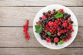 Fresh ripe berries plate on wooden table background with copy space