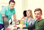 education, technology and school concept - group of smiling students in computer class