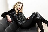 woman wearing fashionable black clothes sitting on a sofa