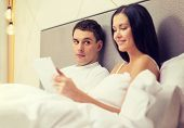 hotel, travel, relationships, technology, intermet and happiness concept - smiling couple in bed with tablet computer