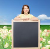 people, advertisement and education concept - happy little girl with blank blackboard