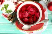 Traditional polish clear red borscht with dumplings and Christmas decorations on color wooden table background