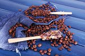 Wooden sticky spoons with coffee beans and crystals on blue wooden background with jeans material
